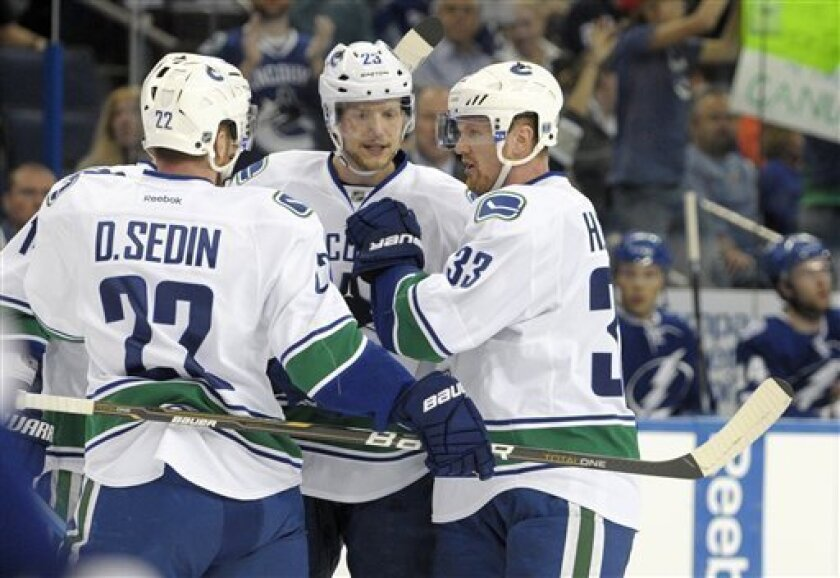 Vancouver Canucks' Alexander Edler, center, is congratulated by teammates Daniel Sedin, left, and Henrik Sedin after scoring a goal during the first period of an NHL hockey game against the Tampa Bay Lightning in Tampa, Fla., Tuesday, Jan. 10, 2012. (AP Photo/Phelan M. Ebenhack)