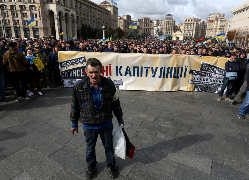"""No to Capitulation,"" reads a banner held by demonstrators in downtown Kyiv, Ukraine, on Sunday."
