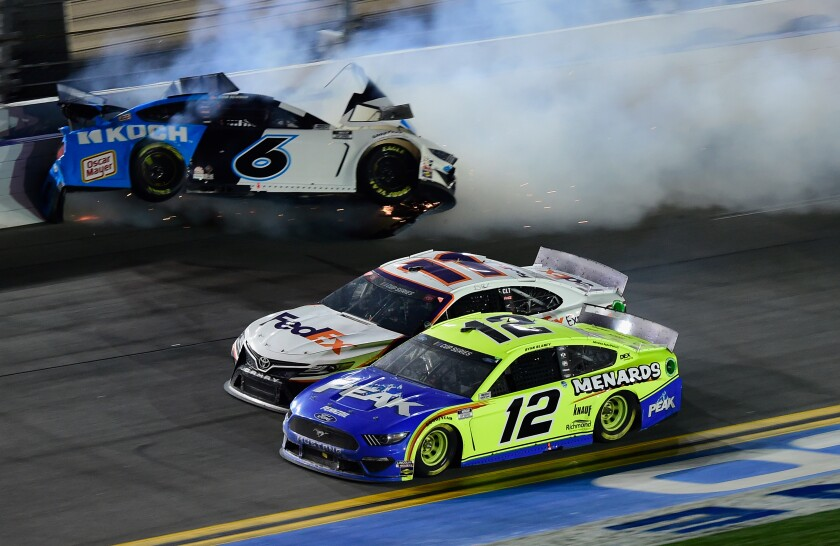 Ryan Newman hits the outside wall as Denny Hamlin, center, beats Ryan Blaney to the finish line to win the Daytona 500 on Monday.