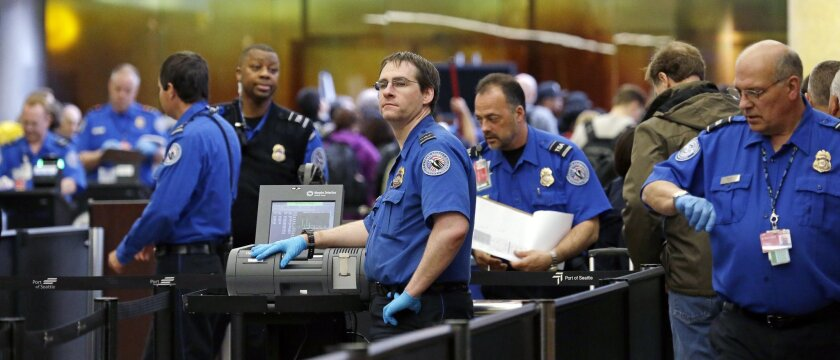 TSA agents work at a security checkpoint at Seattle-Tacoma International Airport in SeaTac, Wash.