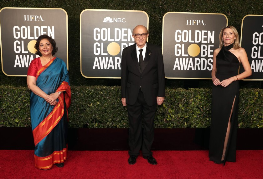 Three people stand on the red carpet at the Golden Globe Awards