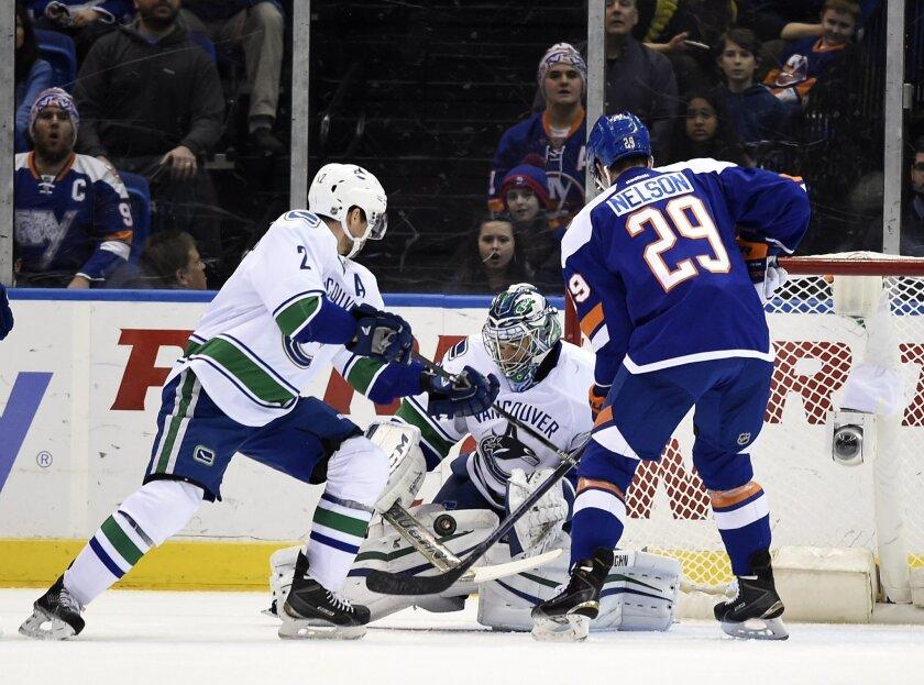 Vancouver Canucks goalie Ryan Miller (30) blocks a shot on goal by New York Islanders center Brock Nelson (29) as Canucks defenseman Dan Hamhuis (2) defends in the first period of an NHL hockey game at Nassau Coliseum on Sunday, Feb. 22, 2015, in Uniondale, N.Y. (AP Photo/Kathy Kmonicek)