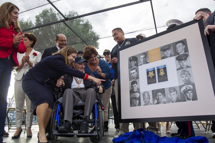 U.S. Congresswoman Loretta Sanchez shows Tibor Rubin a photo of himself as a young man during a Medal of Honor Korean War stamp dedication ceremony during the 2014 Veterans Day celebration at the Orange County Fairgrounds on Tuesday. Rubin, an Army corporal, received the Medal of Honor for his actions in the Korean War.