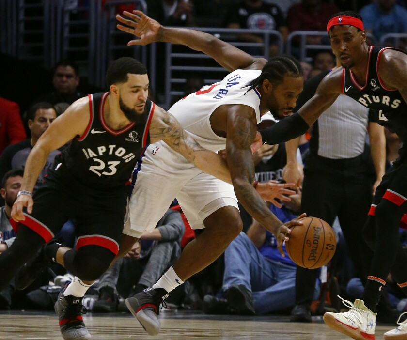 Clippers forward Kawhi Leonard tries to split the defense of Raptors Fred Vanvleet, left, and Rondae Hollis-Jefferson during the fourth quarter of a game Nov. 11 at Staples Center.