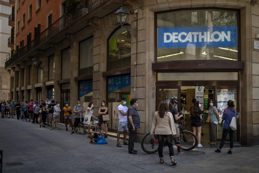 Customers queue outside a sportswear and equipment store during the coronavirus outbreak in Barcelona, Spain, Thursday, June 4, 2020. (AP Photo/Emilio Morenatti)
