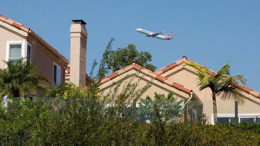 A commercial airplane flies over homes along Upper Newport Bay in Newport Beach after taking off fro