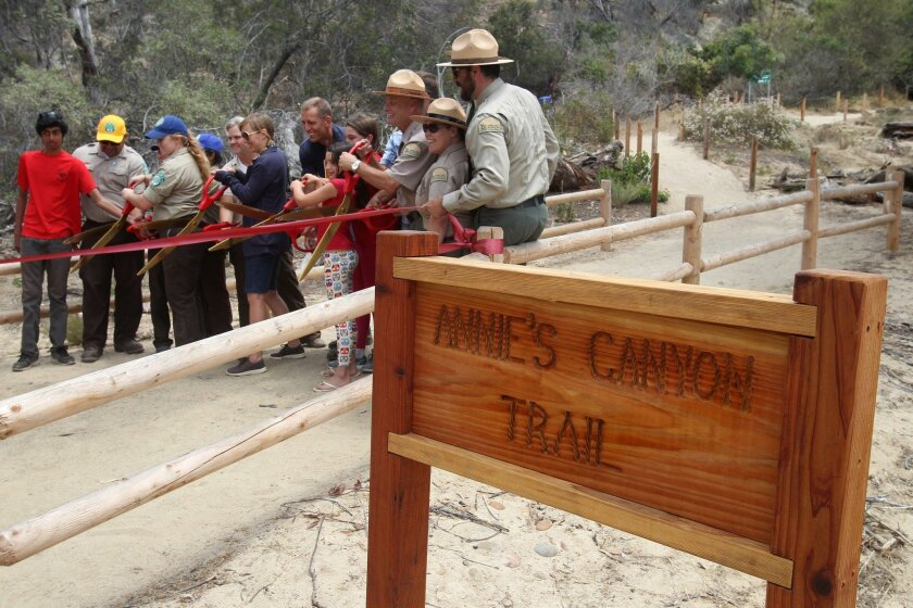 A mixture of interested people cut the ribbon of Annie's Canyon Trail Tuesday, part of the trail's opening ceremony at San Elijo Lagoon Ecological Reserve in Solana Beach and Encinitas.