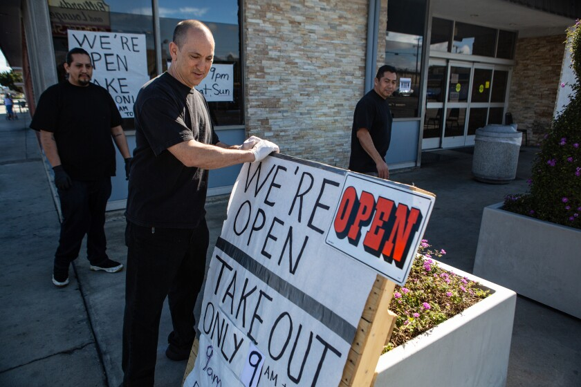 "Gardena Bowl Coffee Shop co-owner Frank Nakano positions a ""We're Open"" sign with new takeout hours."