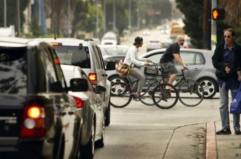 Cyclists, cars and pedestrians at a busy intersection in West Los Angeles.