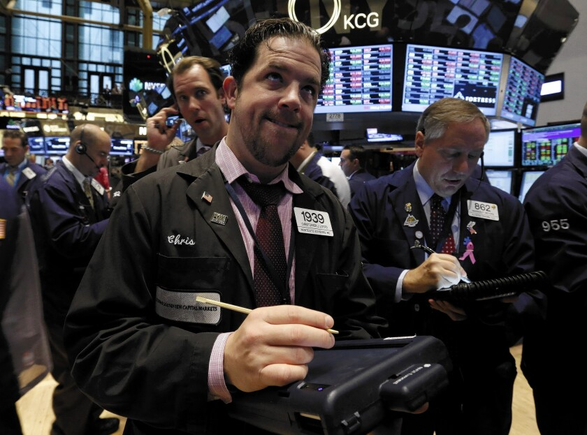 Trader Christopher Lotito, center, works on the floor of the New York Stock Exchange. Studies show that most people don't understand rudimentary principles of finance and investing.