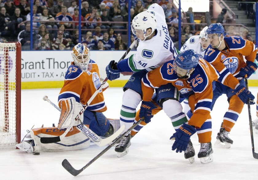 Vancouver Canucks' Brendan Gaunce (50) is stopped by Edmonton Oilers' goalie Cam Talbot (33) as Darnell Nurse (25) defends during the first period of an NHL hockey game, Friday, March 18, 2016 in Edmonton, Alberta. (Jason Franson/The Canadian Press via AP) MANDATORY CREDIT