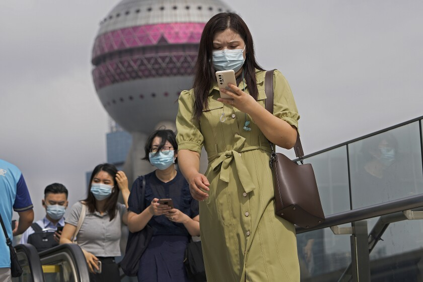 People in masks walk while looking at phones in Shanghai.