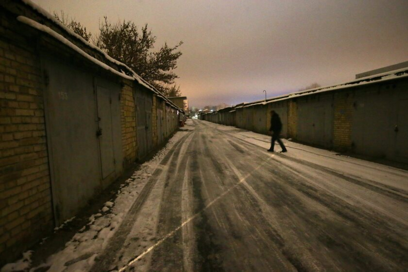 A Ukrainian volunteer walks past garages, some of which are serving as a storehouse for humanitarian aid for Ukrainian soldiers.