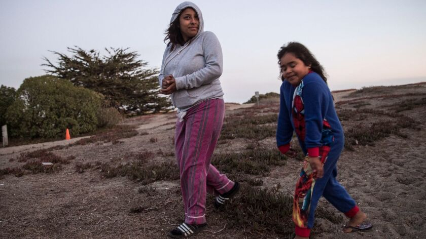 Kelly Ramirez, 17, left, and her sister Briseyda Sandoval, 6, walk along the dunes from their campground at Doran Regional Park in Bodega Bay. Their family is camping at the park to escape the smoke inundating their home in Windsor.