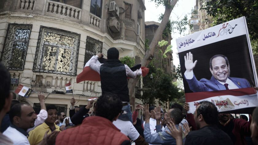 Supporters of Egyptian president Abdel Fattah el-Sisi dance outside a polling station in the Cairo d