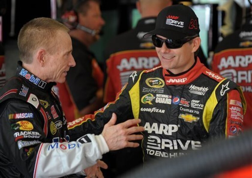Drivers Mark Martin, left, and Jeff Gordon chat in the garage during practice for Sunday's NASCAR Sprint Cup Series auto race at Atlanta Motor Speedway, Saturday, Aug. 31, 2013 in Hampton, Ga. (AP Photo/David Tulis)