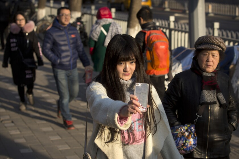 Web performer Wang Weiying, 18, broadcasts a live stream from her smartphone as she walks down a street in Beijing on Feb. 28, 2016.