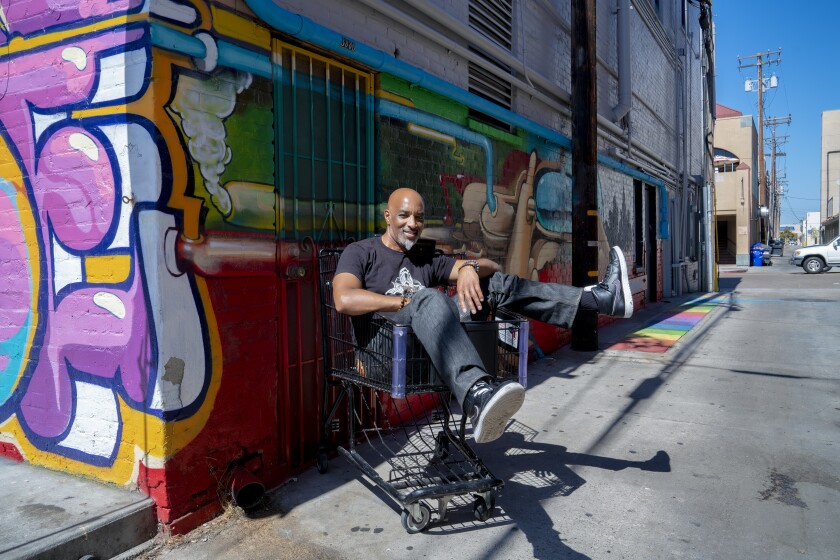 San Diego-based graffiti artist and muralist Maxx Moses is shown with the mural he painted in an alley near the Studio Door Gallery in Hillcrest, where he has a studio. On Oct. 23, he will be giving a talk about self-expression at the Studio Door. The event starts at 7 p.m.