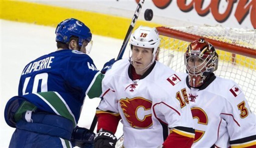 Vancouver Canucks center Maxim Lapierre (40) tries to get a shot past Calgary Flames right wing Tim Jackman (15) and Calgary Flames goalie Henrik Karlsson (35) during second period NHL hockey action at Rogers Arena in Vancouver, British Columbia, Saturday, March, 31, 2012.  (AP Photo/The Canadian P