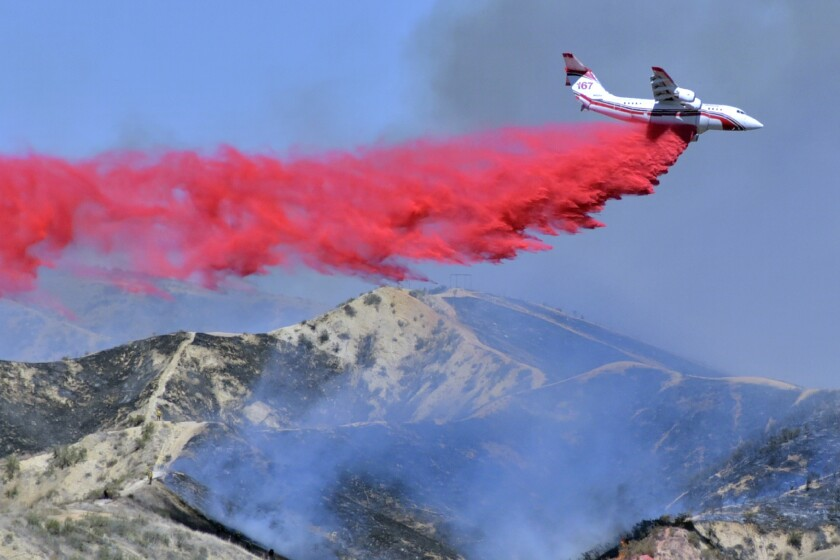 FILE - In this April 28, 2021, file photo, a fixed-wing tanker makes a drop of fire retardant on the North Fire in Castaic, Calif. By aggressively responding to smaller fire, officials said Thursday, May 13, 2021, they hope to minimize the number of larger fires that have become more common as climate change makes the landscape warmer and dryer (Dan Watson/The Santa Clarita Valley Signal via AP, File)