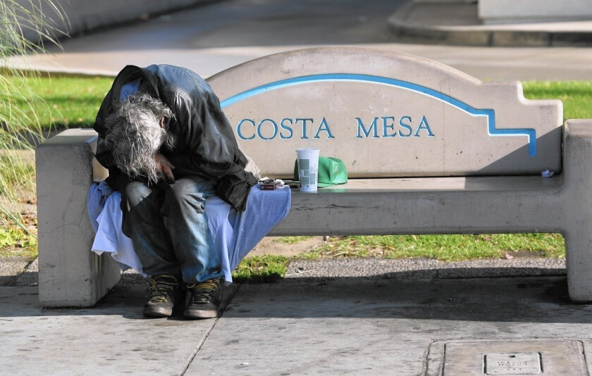 A homeless man sleeps on a bench near Wilson Street and Harbor Boulevard in Costa Mesa. According to a Vanguard University survey, Costa Mesa's homeless population increased 45% between fall 2013 and fall 2015.