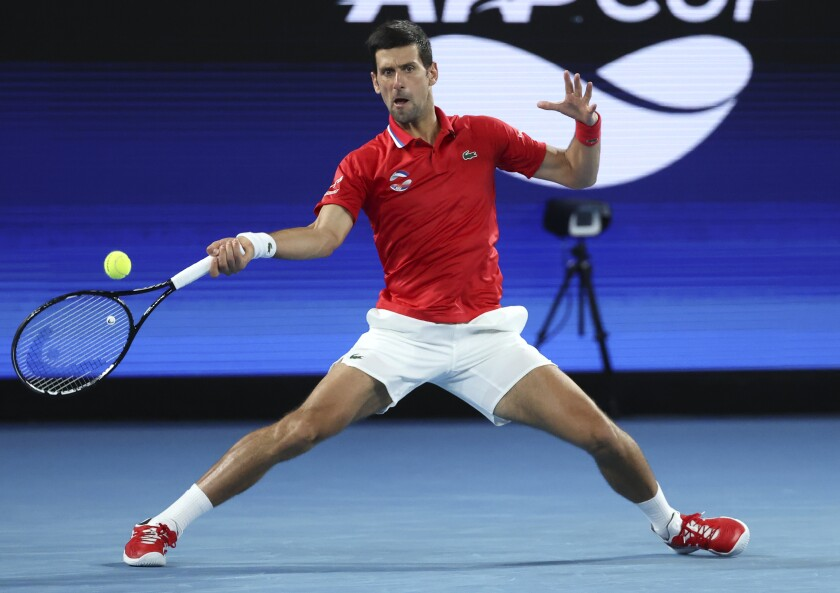 Serbia's Novak Djokovic makes a forehand return to Germany's Alexander Zverev during their ATP Cup match in Melbourne, Australia, Friday, Feb. 5, 2021.(AP Photo/Hamish Blair)