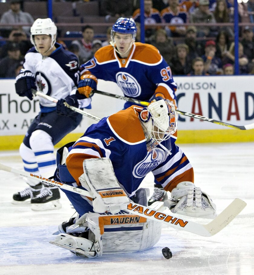 Winnipeg Jets' Nikolaj Ehlers (27) is stopped by Edmonton Oilers goalie Laurent Brossoit (1) as Connor McDavid (97) defends during the first period of an NHL hockey game Saturday, Feb. 13, 2016, in Edmonton, Alberta. (Jason Franson/The Canadian Press via AP)