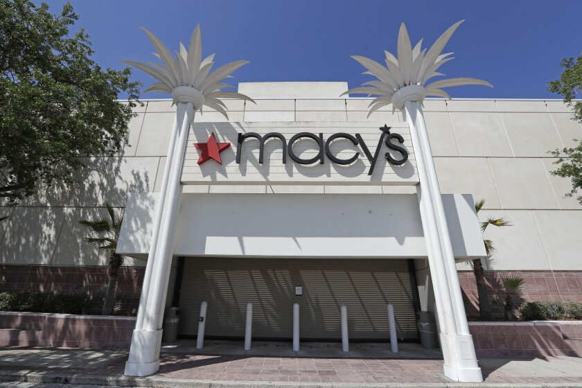FILE - In this March 30, 2020 file photo, the entrance to a Macy's department store is closed behind barriers and storm shutters remains closed in Orlando, Fla. Macy's reports preliminary earnings on Tuesday, June 9. (AP Photo/John Raoux, File)