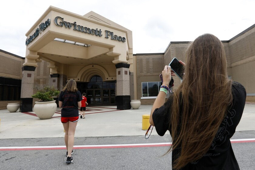 """FILE - In this July 23, 2019 file photo, Brinley Rawson, a 17-year-old Stranger Things fan from Gwinnett County, snaps a photo of Gwinnett Place Mall in Duluth, Ga. The Georgia mall heavily featured in the latest season of Netflix's """"Stranger Things"""" is going up for sale. Moonbeam Capital Partners is ready to sell its portion of the long-struggling Gwinnett Place Mall, which has been so empty that a body went unnoticed near the food court for about two weeks in 2017. (AP Photo/Andrea Smith, File)"""