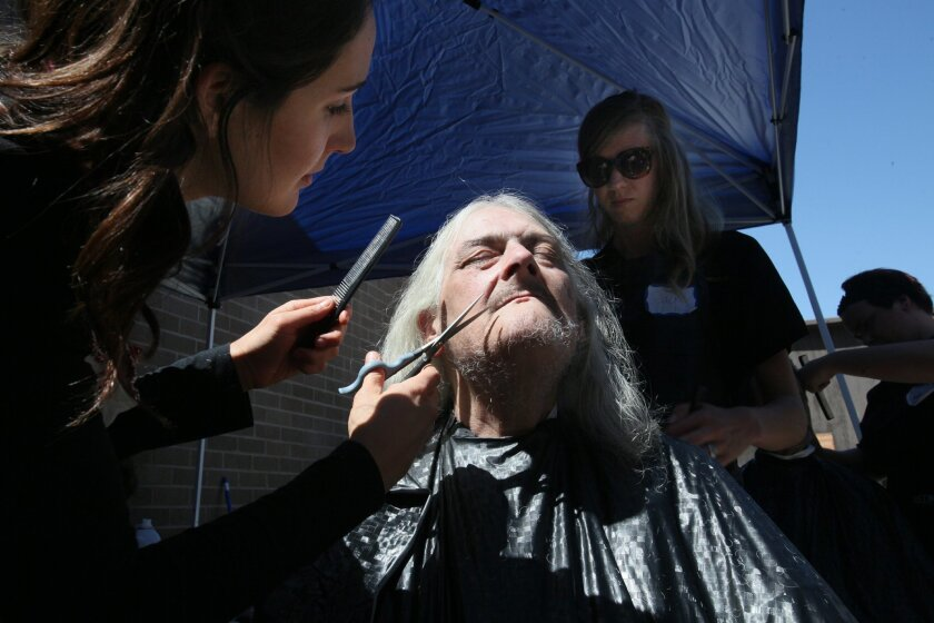 James Taylor sat in the barber's chair while Staci Tresser, left, and Jackie Crosby, background right, trimmed his beard and cut his hair for him at the Project Homeless Connect East County earlier this year. A similar Homeless Connect will be held at Bread of Life in Oceanside on Saturday.