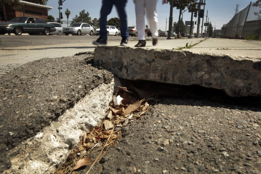 Two people use the sidewalk along Vermont Avenue at the 101 Freeway.