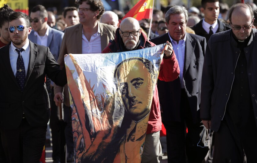 FILE - In this Oct. 24, 2019 file photo, a man holds an image of Spanish dictator Gen. Francisco Franco during a gathering outside the Mingorrubio cemetery where Franco is now laid to rest, on the outskirts of Madrid. The Socialist-led coalition government's Cabinet on Tuesday July 20, 2021, approved a draft bill that takes aim at anyone who extols Franco's coup and the dictatorship or extols its leaders. (AP Photo/Manu Fernandez, File)