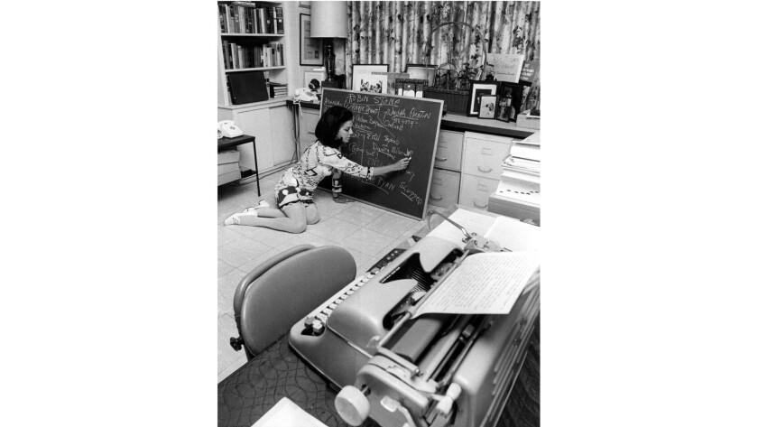Jacqueline Susann charts her novel-in-progress, 'The Love Machine, ' wearing a 1960's print shift.
