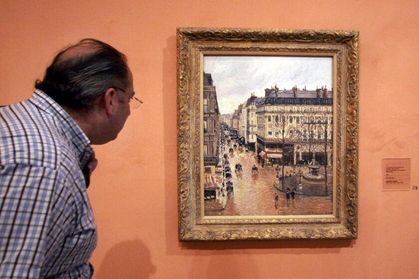 "A visitor to the Thyssen-Bornemisza Museum in Madrid looks at ""Rue St.-Honore, Apres-Midi, Effet de Pluie."""