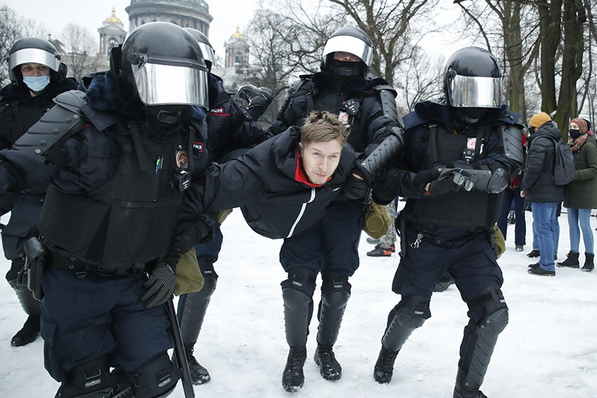 A man is detained by law enforcement outside in the snow.
