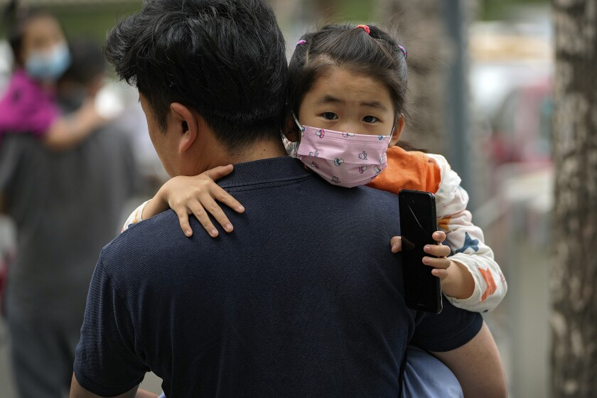A man carries a child to a school in Beijing.