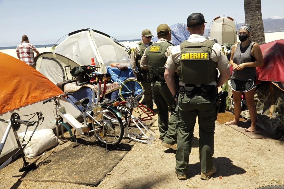 Sheriff's deputies walk amid a homeless encampment in Venice.