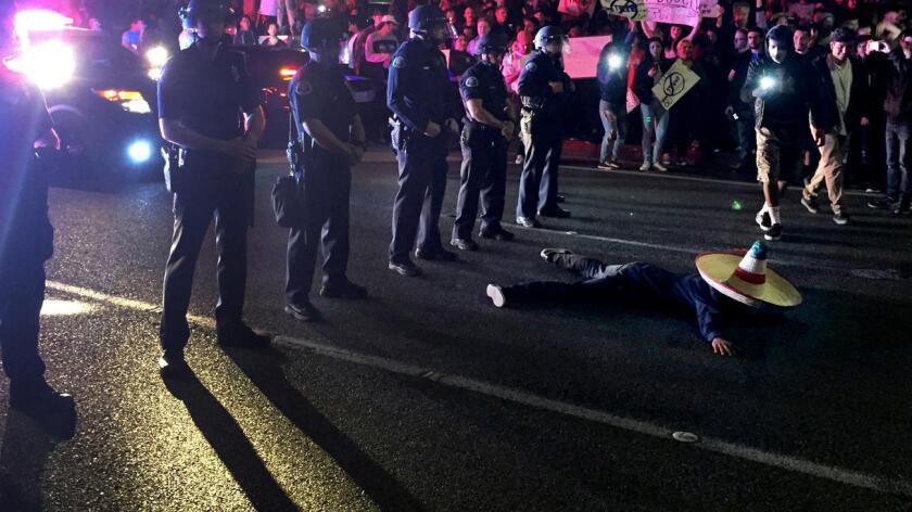 Un manifestante anti Trump, sobre el suelo en la intersección de Fair Drive y Fairview Road, cerca del Pacific Amphitheatre, donde el candidato hizo su primera aparición en campaña en California (Gina Ferazzi/Los Angeles Times).