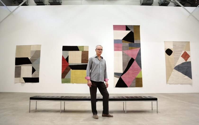 Artist in residence Mike Berg stands before his installation of Turkish kilims at the Museum of Contemporary Art.  Berg creates the designs and collaborates with traditional Turkish weavers to create the pieces. Berg says that he looks at them as paintings, with a more interesting and complex surfa