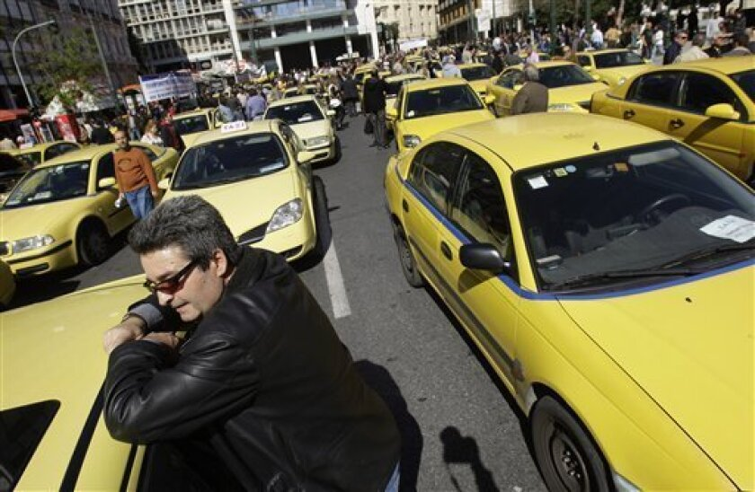 Taxi drivers demonstrate outside the Greek Finance Ministry, during their 48-hours strike,in Athens, Tuesday, March 2, 2010. Greece will wait to see how markets react to tougher austerity measures demanded by the European Union before deciding on when to issue new state bonds, a government official said Tuesday. (AP Photo/Petros Giannakouris)
