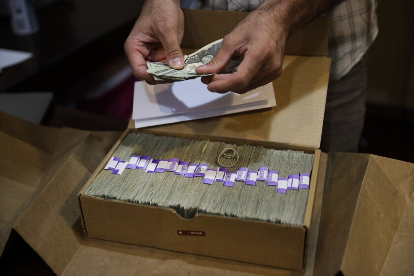 In file photo, the owner of a medical marijuana dispensary in Los Angeles prepares his monthly tax payment -- paid in cash because of a lack of access to financial services.