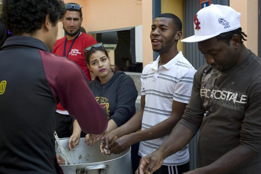 Miclisse Noel, 28, second from right, a migrant from Haiti, chats with volunteers at the Desayunador Salesiano Padre Chava shelter on June 8, 2016, in Tijuana, Mexico. He plans to go to the San Ysidro Port of Entry, where they will present themselves to U.S. immigration and seek asylum. To the right is Makendy Changeux, also from Haiti. (Photo - David Maung)