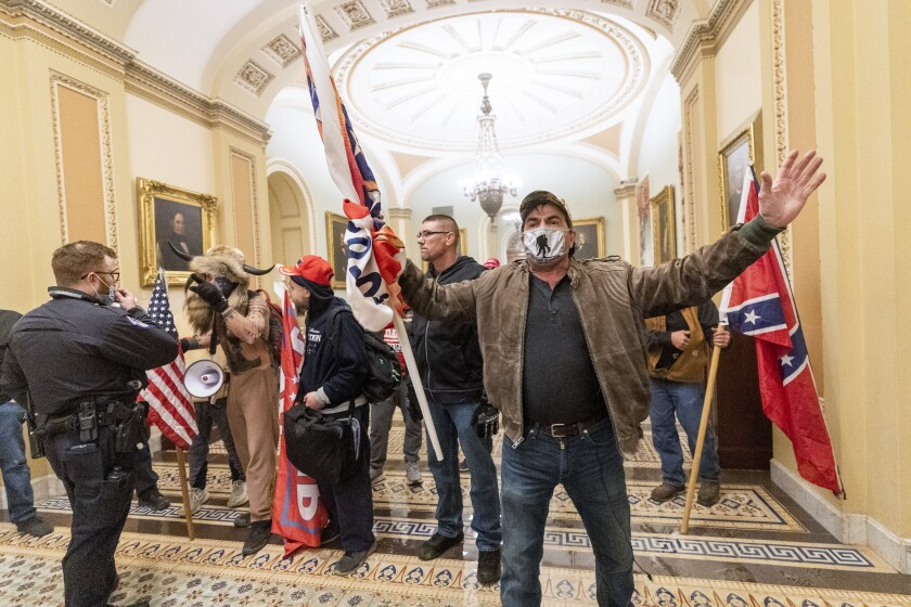 U.S. Capitol Police officers confront pro-Trump rioters outside the Senate Chamber.