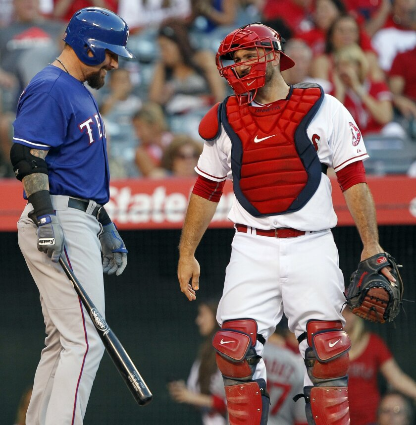 "Texas Rangers' Josh Hamilton, left, and Los Angeles Angels catcher Chris Iannetta react as Hamilton is greeted with ""Boos"" as he is introduced to bat during the second inning of a baseball game in Anaheim, Calif., Friday, July 24, 2015. It was Hamilton's first game in Anaheim since being traded to the Rangers from the Angels. (AP Photo/Alex Gallardo)"
