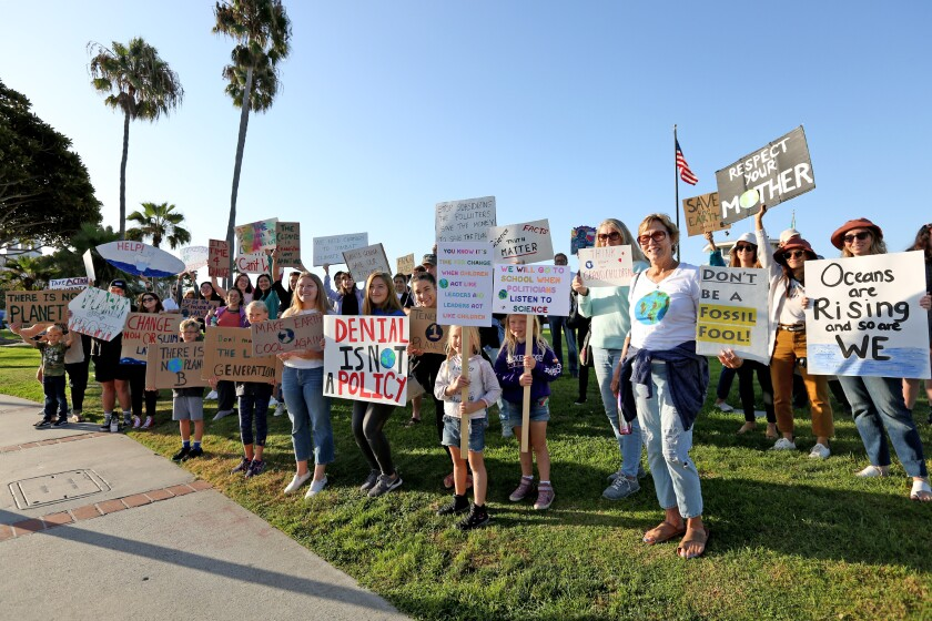 People hold protests sign during the Climate Strike climate change protest in Laguna Beach.