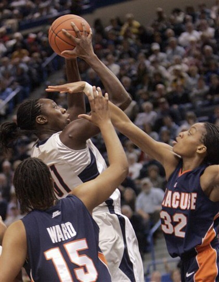 Connecticut's Tina Charles, top left, goes up for a shot as Syracuse's Juanita Ward (15) and Nicole Michael (32) defend during the first half of an NCAA college women's basketball game in Hartford, Conn., Saturday, Jan. 17, 2009.   (AP Photo/Bob Child)