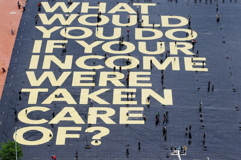 """FILE - In this May 14, 2016 file pictire a huge poster reading """"What would you do if your income were taken care of?"""" is pictured on the Plaine de Plainpalais square in Geneva, Switzerland.  The poster hints at a national referendum on June 5, were Swiss voters will have to decide on the introducti"""