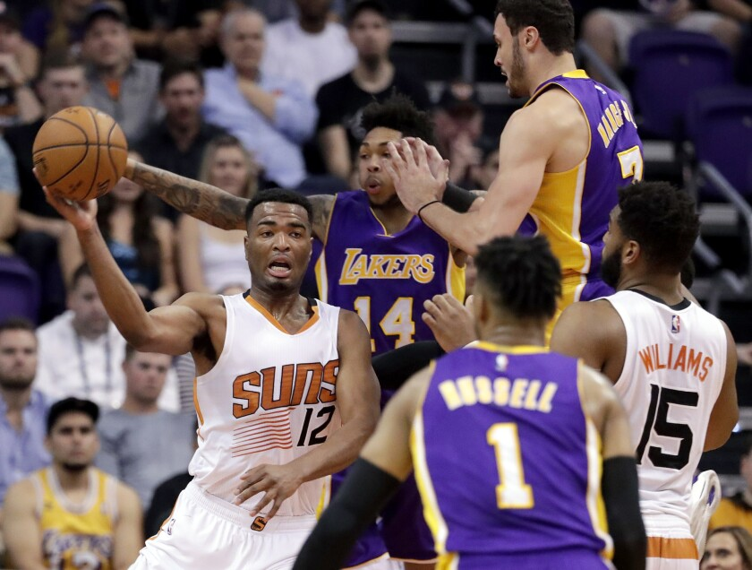 Suns forward T.J. Warren passes the ball away from Lakers forward Brandon Ingram (14) as forward Larry Nance Jr. (7) and guard D'Angelo Russell (1) defend during the first half of a game on March 9.
