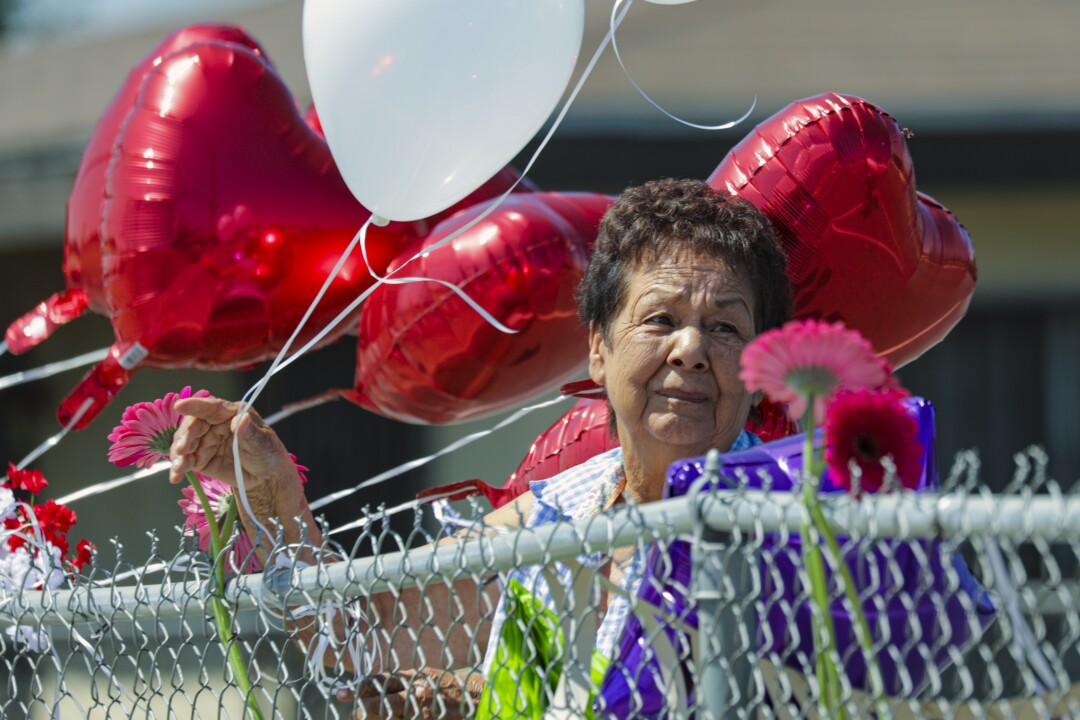 Mercy Aguirre ties balloons in memory of her longtime colleague Lucy Reyes.