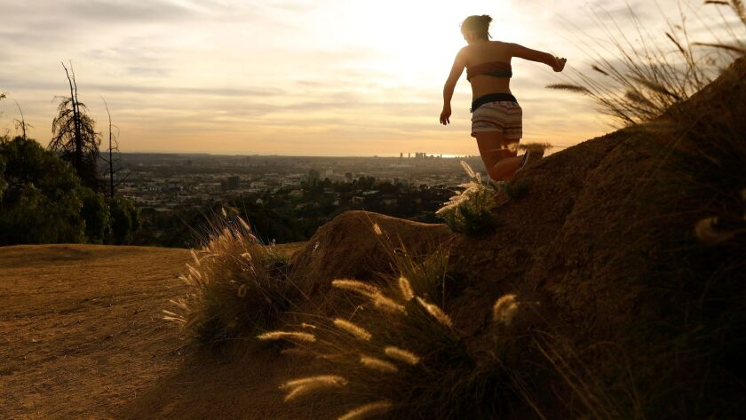 LOS ANGELES-CA-JANUARY 29, 2018: A woman runs in Griffith Park at sunset in above 80 degree temperat